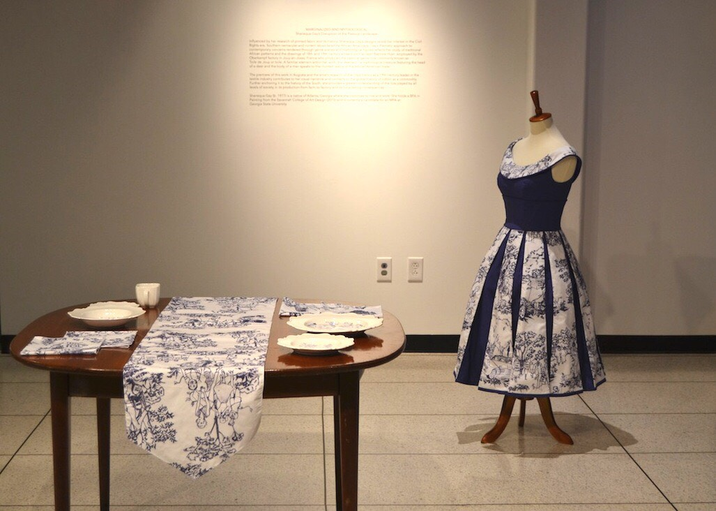 photo of a table with blue and white table linen and a tea set on top with a 1950s-style dress in the background