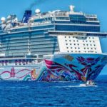 photo of a white cruise ship with a colorful mural on the ocean